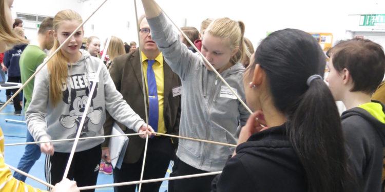 Oppilaat rakentavat tikuista geometrisen kappaleen.