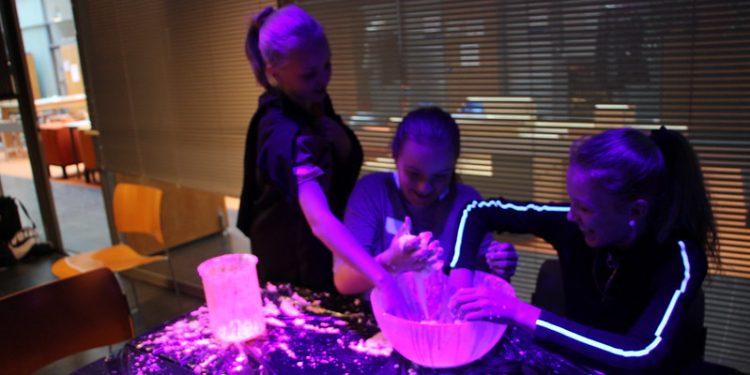 Oppilaat tekevät tutkimusta hyödyntäen UV-valoa.