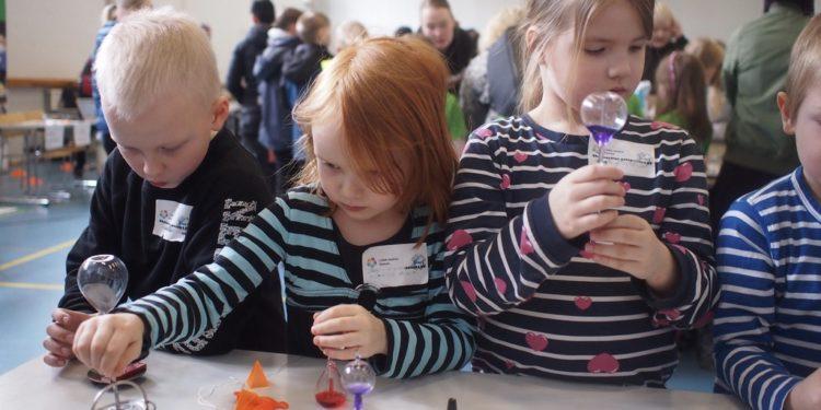 Lapset tutkivat tiimalaseja.
