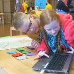 Kaksi lasta katsoo tietokonetta StarT-festareilla.